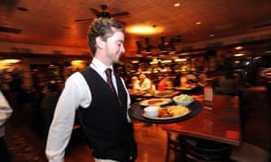 A waiter rushes with a tray of food