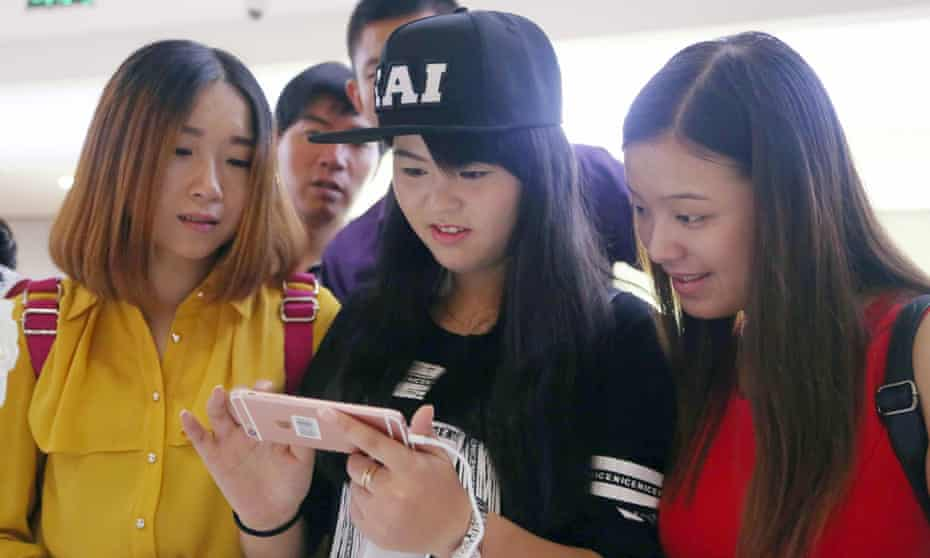 A customer, surrounded by her female friends, tries out a rose gold Apple iPhone 6s smartphone at a branch of China Unicom in Shanghai, China