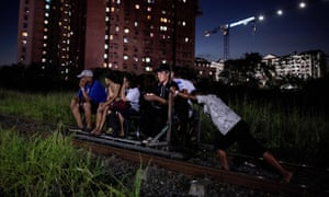 A trolley boy pushing a homemade cart carrying passengers on a train track in Manila