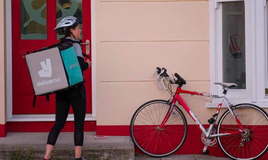 young woman delivering Deliveroo meal to a house with her bicycle alongside
