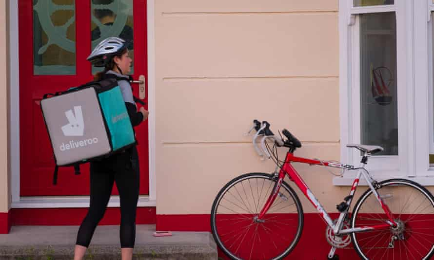 A food delivery courier knocks on a door