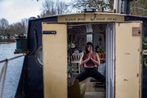 Oxford, England. Yoga teacher Harriet McAtee, who is 6ft tall, in Utkata Konasana pose during a class on her 6ft-wide narrowboat. The pandemic has forced her to conduct her classes via Zoom