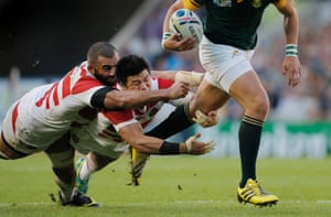 Michael Leitch and Fumiaki Tanaka of Japan try to stop Handre Pollard during the South Africa v Japan Pool B Rugby World Cup match at Brighton Community Stadium in September 2015.