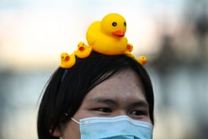 A protester wears a hairband with rubber ducks