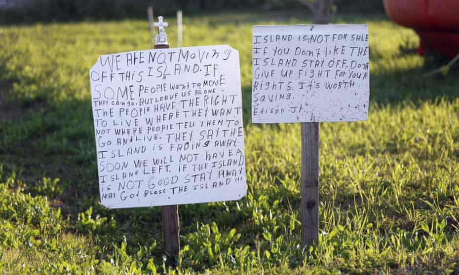 A defiant sign is posted next to a survival pod from an oil rig.