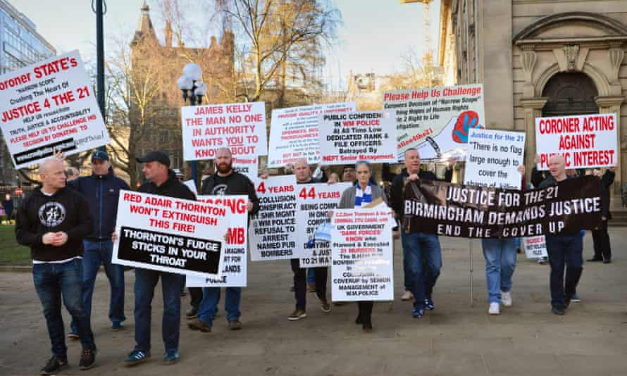 People carry placards in St. Philip's Cathedral Square before the first day of the inquest into the Birmingham Bombings