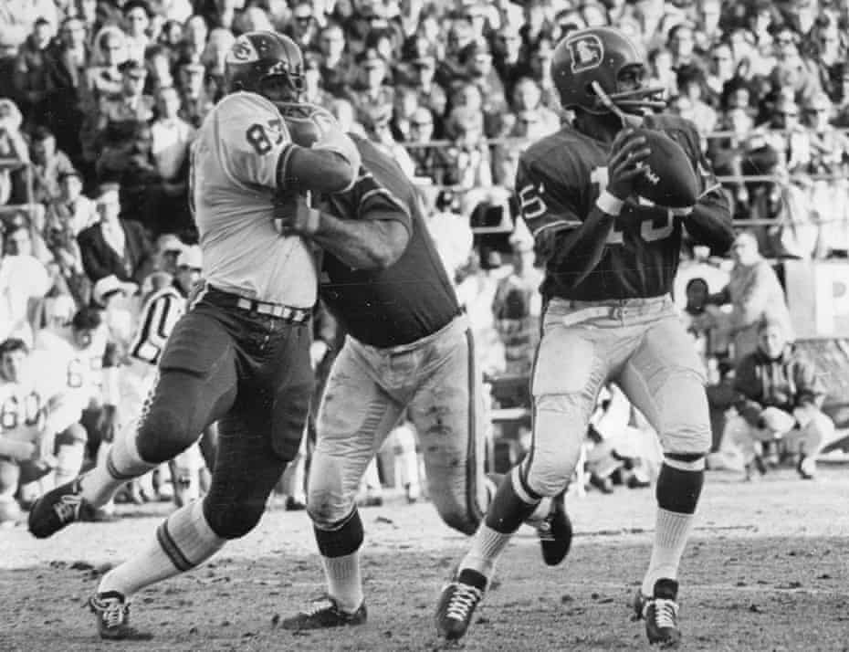 Denver Post ArchivesDEC 14 1968, DEC 15 1968 Denver Broncos (Action) Denver quarterback Marlin Briscoe is unaware that a battle is occurring behind him in the first quarter Saturday. Denver's Sam Brunelli is shown holding Kansas City's Aaron Brown while Briscoe prepares to let loose with a pass. Credit: Denver Post (Denver Post via Getty Images)