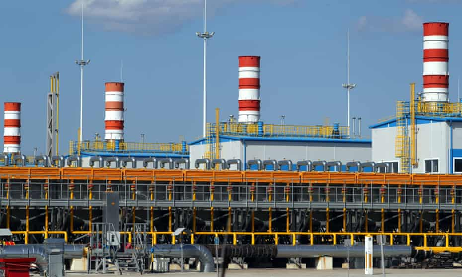 Gazprom's Slavyanskaya compressor station, the starting point of the Nord Stream 2 pipeline. The image shows four red and white striped smokestacks above white buildings with blue roofs