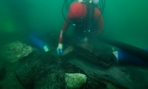 An archaeologist inspects the keel of a shipwreck discovered in the waters around the sunken port-city of Thonis-Heracleion.