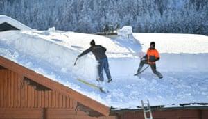 Men shovel snow from a roof in Untertauern, Austria