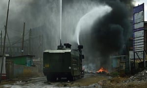 A police truck with a water cannon extinguishes a burning barricade in Kibera.