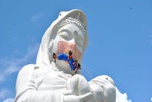 Workers place a mask on a 57-metre Buddhist goddess statue in Aizuwakamatsu, Japan