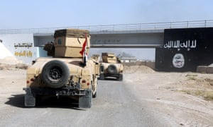 Iraqi military vehicles pass an Isis flag in the Golan district of Falluja.