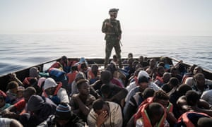 A Libyan coastguardsman stands on a boat carrying  migrants off the coastal town of Zawiyah