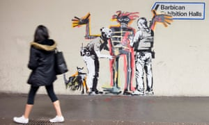 A woman passes one of the Banksy murals near the Barbican Centre.
