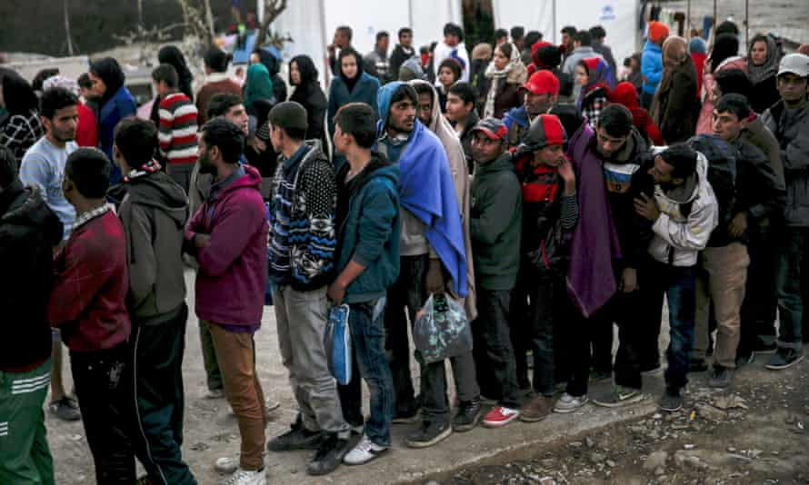 Refugees and migrants line up for a food distribution at the Moria refugee camp on the Greek island of Lesbos.