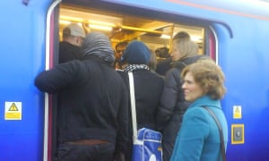 People attempt to get on the train at Hornsey station.