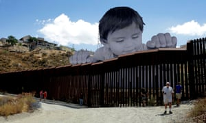 An art installation created by French artist JR rises above and appears to peek over the border wall that bisects Tecate, Mexico and Tecate, California, USA.