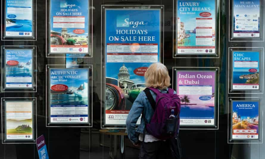 A woman looking at posters showing Saga holidays in the window of a travel agents in Cirencester, Gloucestershire