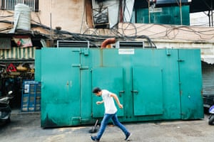 A man walks by a set of generators in Beirut.
