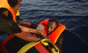 A migrant from Eritrea is helped after jumping into the water from a crowded wooden boat.
