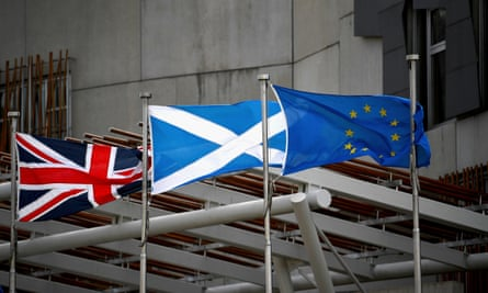 Saltire, union jack and EU flags flutter in the wind outside the Scottish parliament