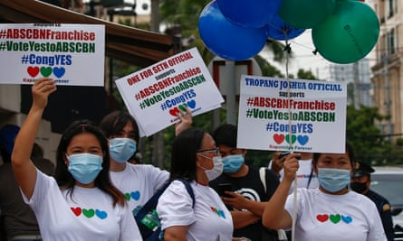 Supporters of ABS-CBN hold signs outside the network's headquarters in Quezon City in Manila