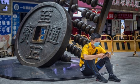 A man uses his cellphone as he sits next to a sculpture representing the Chinese yuan in Guangzhou, Guangdong province.