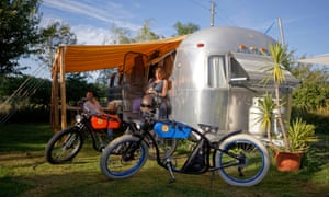 Two people outside and Airstream caravan with bikes in the foreground at Airstream Europe trailer park in France.