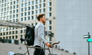 Shot of a young businessman traveling through the city with his bicycle.