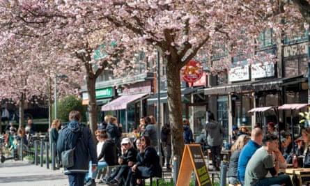 Scores of people sit outside cafés in Stockholm, Sweden.