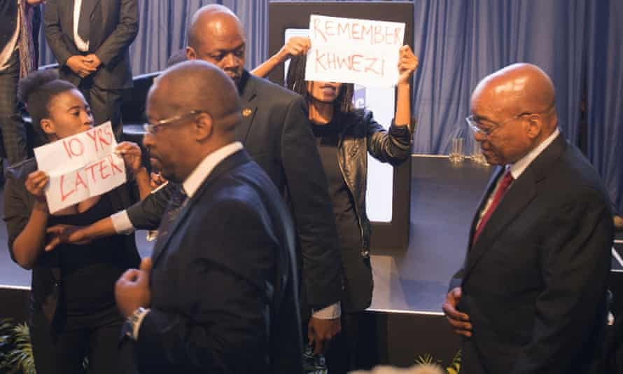Security guards escort Zuma paast the protesters.