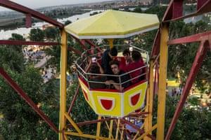 Young Iraqis ride a ferris wheel.