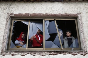 Gaza City, Gaza: Palestinian children pull shards of glass from a broken window at their home near the site of Israeli overnight attacks