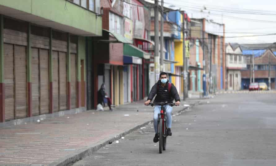 A man cycles past shuttered businesses during a strict lockdown in Bogota, Colombia.