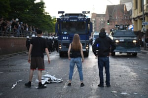 Three people stand in front of police vehicles during the Welcome to Hell protest march, which took place on the eve of the G20 summit