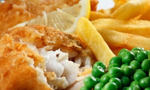 Closeup of fish and chips with peas and a slice of lemon.
