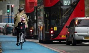 Children travelling by  bike to school in heavy London traffic