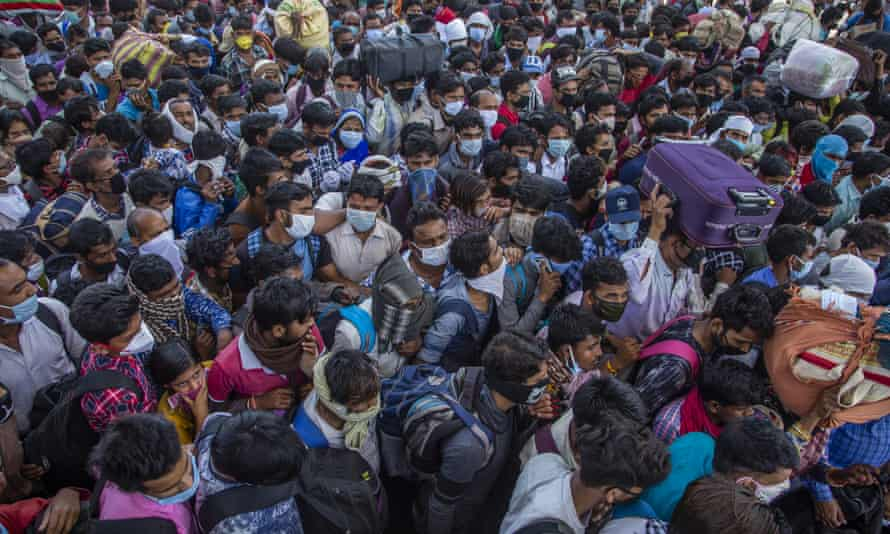 Crowds try to board buses out of the capital, Delhi.