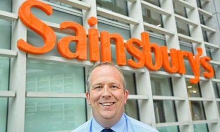 Simon Roberts photographed smiling beneath a large Sainsbury's sign