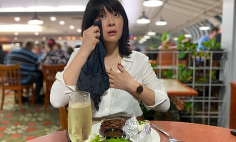 Michelle Law says farewell to Sizzler, holding a  paper napkin to her watering eye