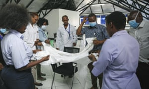 A health inspection officer shows Kenyan doctors how to use protective equipment