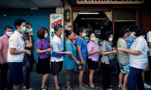 A Thai official distributes queue tickets to people standing in line to buy face masks outside a pharmacy in Bangkok, Thailand, 04 March 2020. Thailand is facing a shortage of masks and hand sanitizers as people have been panic buying these items over fear of a coronavirus outbreak in the country.