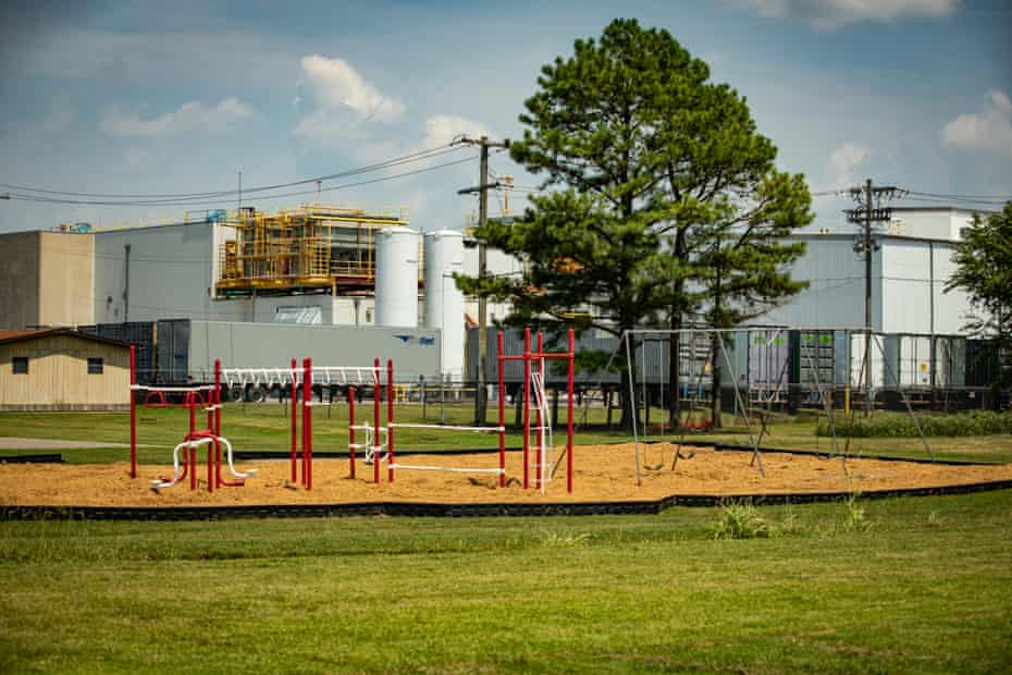 The Tyson Foods Green Forest processing plant is seen from a playground.