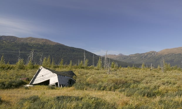 A house has collapsed into the ground as the permafrost melts beneath it, near Portage Glacier, Alaska
