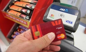 Hand holding MasterCard about to use an EFTPOS machine.