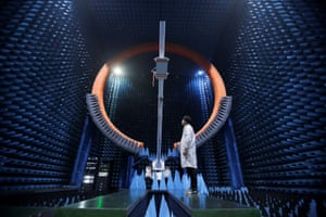 An engineer stands under a base station antenna of 5G in Huawei's SG178 sphere at its Manufacturing Center