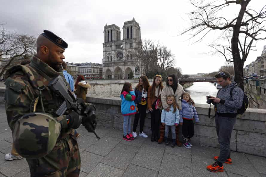 French soldier patrols as people arrive for the Easter mass at Notre Dame Cathedral in Paris