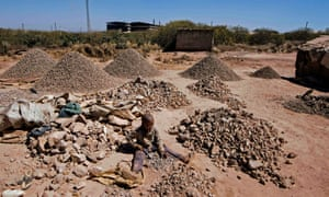 A child breaks rocks extracted from a cobalt mine in the DRC.