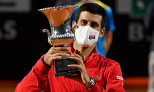 A masked Novak Djokovic celebrates with the trophy after beating Diego Schwartzman of Argentina in the final of the Rome Masters